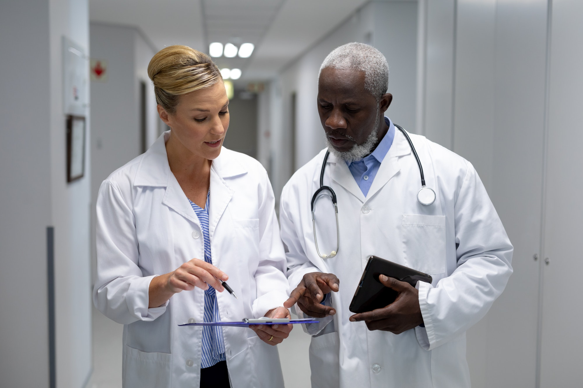 Diverse male and female doctors standing in hospital corridor looking at medical chart document